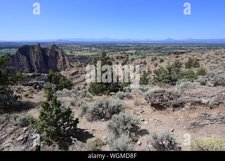 View of Terrebonne and distant volcanoes from Misery Ridge Trail in Smith Rock State Park, Oregon on a clear cloudless summer day. - Stock Photo
