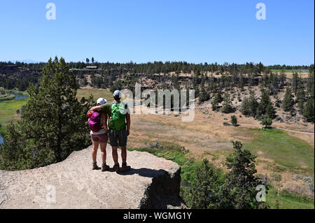 Young couple enjoying view from Misery Ridge Trail in Smith Rock State Park, Oregon on clear cloudless summer day. - Stock Photo