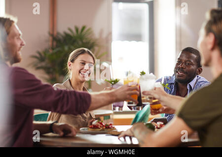 Multi-ethnic group of friends clinking glasses while sitting at table in cafe enjoying cold refreshing drinks, copy space