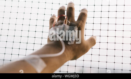 Cropped Hand With Iv Drip Touching Fence - Stock Photo