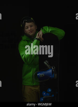 Portrait Of Young Man With Snowboard Standing Against Black Background - Stock Photo