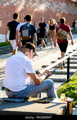Artist painting en plein air on the street by Wawel Hill in Krakow, Poland - Stock Photo