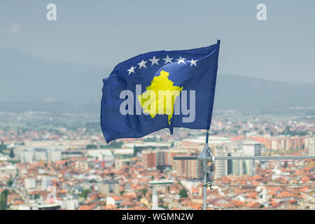 waving flag of Kosovo in front of blurred city - Stock Photo