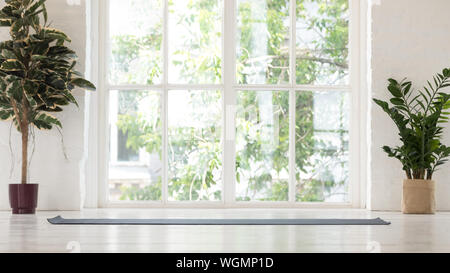 Empty yoga studio interior with windows and unrolled mat - Stock Photo