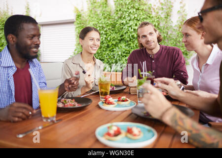 Portrait of multi-ethnic group of friends enjoying lunch together sitting at table in cage and laughing happily, copy space - Stock Photo