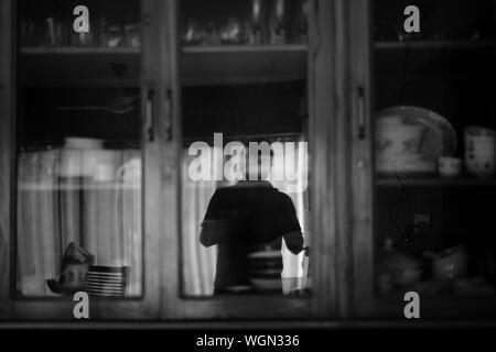 Reflection Of Silhouette Man On Shelf