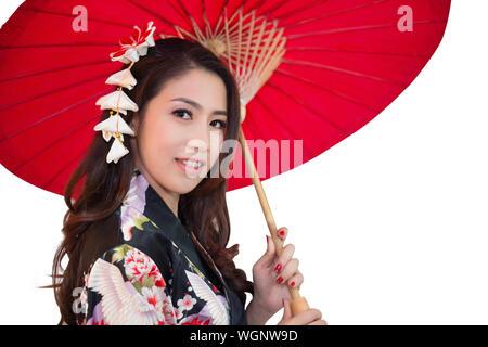 Portrait Of Beautiful Woman In Kimono Holding Red Umbrella Against White Background - Stock Photo