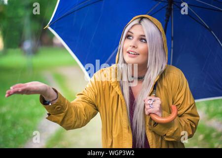 Young Woman With Blue Umbrella Enjoying Rain On Field