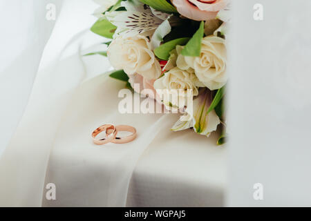High Angle View Of Wedding Rings And Flower Bouquet On Table - Stock Photo