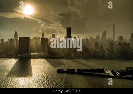 Skyscrapers In Manhattan By East River Against Sky During Sunrise - Stock Photo