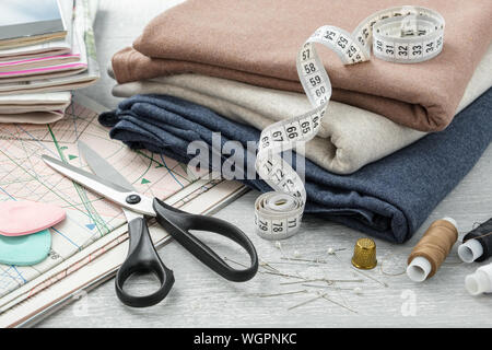 Sewing items: colorful fabrics, scissors, measuring tape, thimble, spools of threads, including pins, chalks, sewing pattern and magazines on a tablet