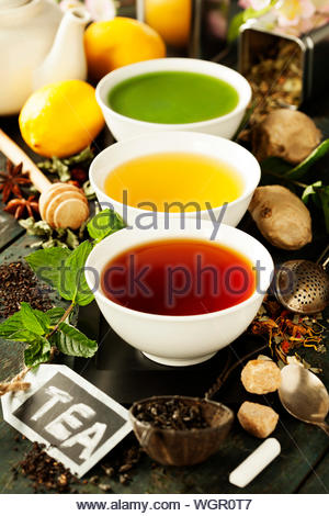 Tea concept. Different kinds of tea in ceramic bowls and ingredients on wooden background - Stock Photo