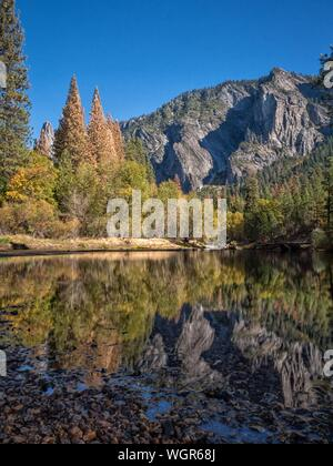 Reflection Of Trees And Rocky Mountains On Calm Lake At Yosemite National Park - Stock Photo