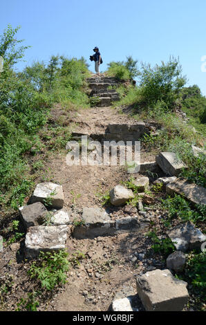 Distant View Of Woman Standing On Ruined Great Wall Of China At Gubeikou - Stock Photo