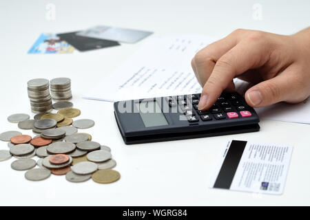 Cropped Image Of Hand Calculating Finance On White Background - Stock Photo