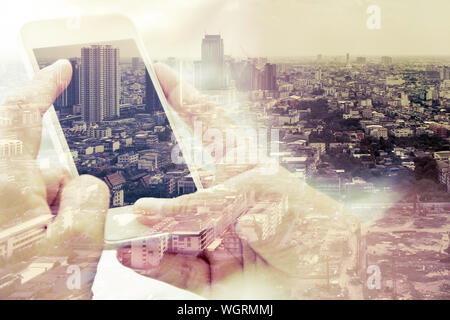 Digital Composite Image Of Hands Holding Smart Phone Against Cityscape - Stock Photo