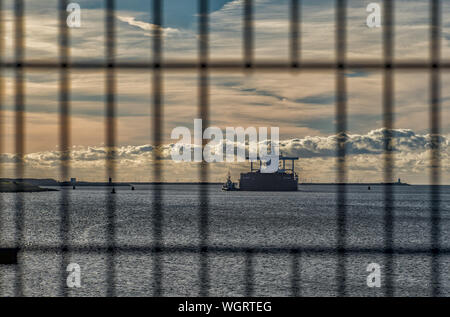 Boat Moving In Sea Seen Through Fence Against Cloudy Sky During Sunset - Stock Photo