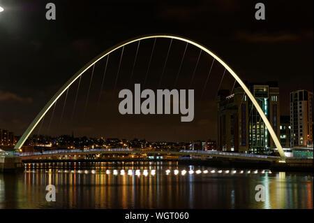Illuminated Gateshead Millennium Bridge Over River At Night - Stock Photo