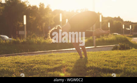 Yoga is the best holistic workout. Mental and physical health. Yoga instructor with do sport. Girl performs yoga in a park on International Yoga Day - Stock Photo