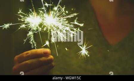 Close-up Of Hand Holding Firework Display At Night - Stock Photo