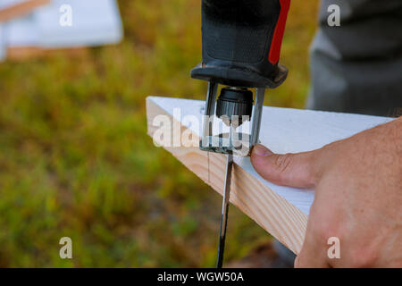 Handmade carpenter engaged in processing wood in the jigsaw - Stock Photo
