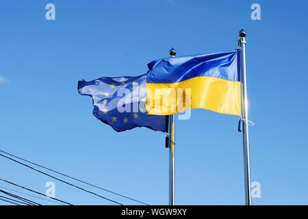 Low Angle View Of Flags Waving Against Blue Sky - Stock Photo
