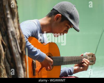Side View Of Young Man Playing Acoustic Guitar Against Lake - Stock Photo