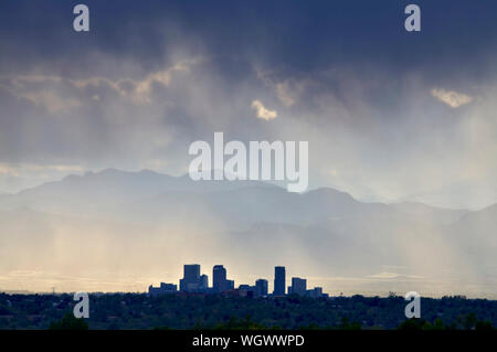 Denver Colorado's skyline facing west with the front range mountains in the background during a rain shower. - Stock Photo