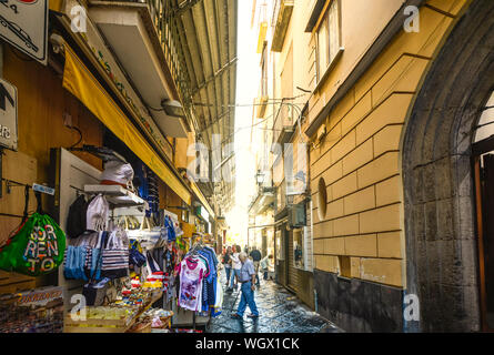 A narrow back alley in Sorrento Italy with an outdoor market selling gifts and souvenirs as tourists and locals shop - Stock Photo