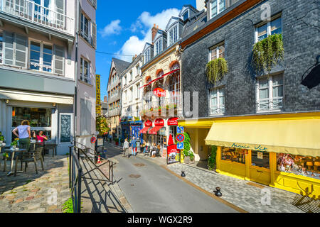 Tourists enjoy the sidewalk cafes and colorful shops in the coastal fishing village of Honfleur, France, on the Normandy Coast. - Stock Photo