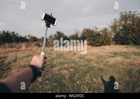 Cropped Hand Of Man Taking Selfie Through Mobile Phone - Stock Photo