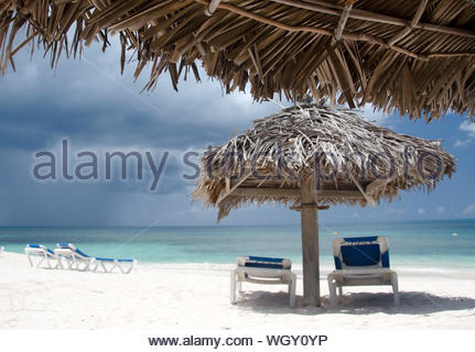 Lounge Chairs And Parasols On Sandy Beach Against Sky - Stock Photo