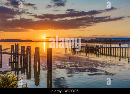 View on Lake Trasimeno at sunset with some people walking along a dock - Stock Photo