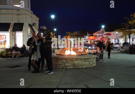 South Windsor CT USA. Nov 2018. Family at night posing taking selfies with ice cream cones by a nice warm fire pit at an outdoor mall. - Stock Photo