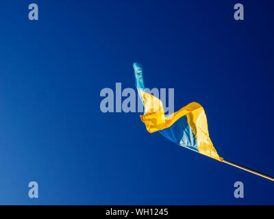 Low Angle View Of Ukrainian Flag Waving Against Clear Blue Sky - Stock Photo