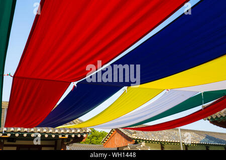Low Angle View Of Colorful Fabric Decorations Hanging By Houses - Stock Photo