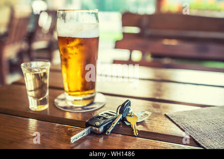 Car keys and glass of beer or distillate alcohol on table in pub or restaurant