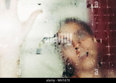 Close-up Of Young Woman In Bathroom Seen Through Wet Window - Stock Photo