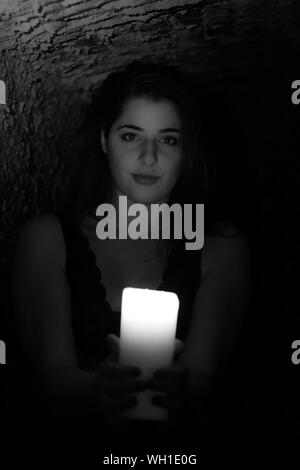 Portrait Of Beautiful Young Woman Holding Lit Candle In Cave - Stock Photo