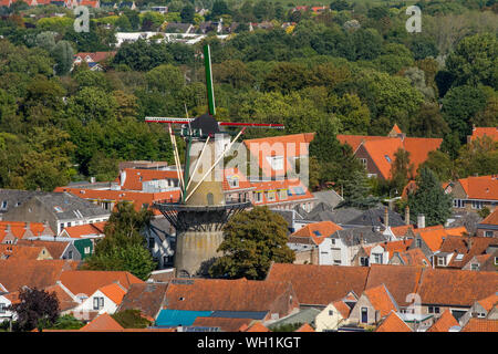 Zierikzee, Zeeland, Netherlands, September 2018: classic and old fashioned and typical Dutch windmill De Hoop rising up above the houses of the villag - Stock Photo
