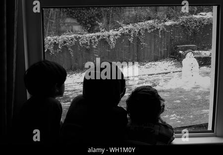 Rear View Of Siblings Looking At Snowman Through Window At Home - Stock Photo