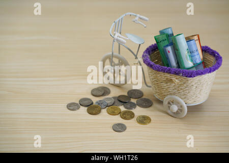 Paper Currencies In Toy Bicycle Basket By Coins On Wooden Table - Stock Photo