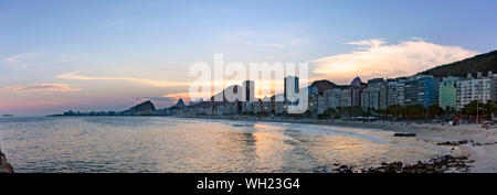 Panoramic photo of Leme and Copacabana beaches in Rio de Janeiro during sunset with its buildings, but the mountains in the background - Stock Photo