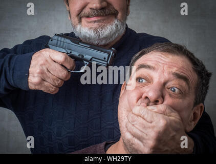 Senior Man Aiming Gun While Covering Victims Mouth - Stock Photo