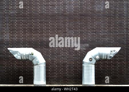 Close-up Of Exhaust Pipes Against Brick Wall - Stock Photo