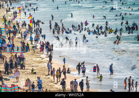 Holidaymakers enjoying themselves on a busy and crowded Fistral Beach in Newquay in Cornwall. - Stock Photo