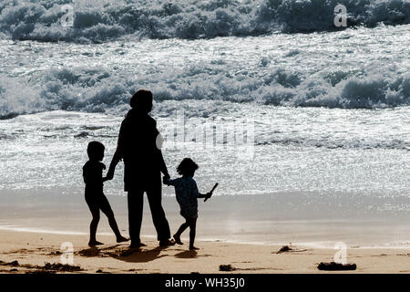 A mother and her two children seen in silhouette as they stand on the shoreline on Fistral Beach in Newquay in Cornwall. - Stock Photo