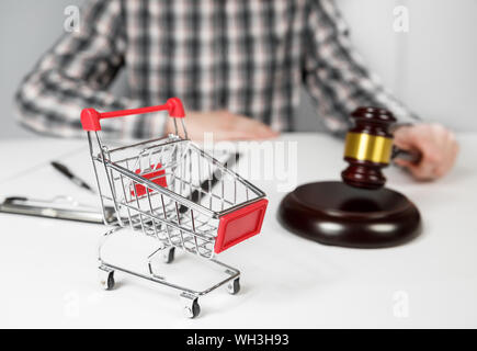 Shopping cart and auction hammer - Stock Photo