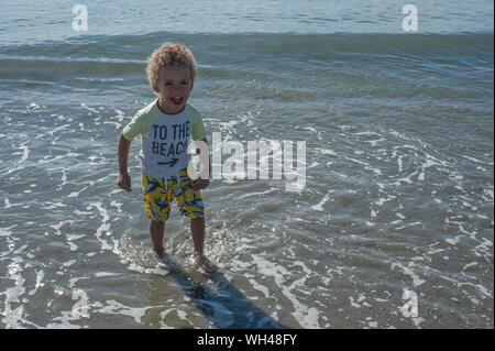 Playful Boy Standing In Shallow Water At Beach - Stock Photo