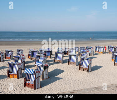 man in red shirt checks beach korbs on the island of norderney in germany on sunny day with blue sky in summer - Stock Photo